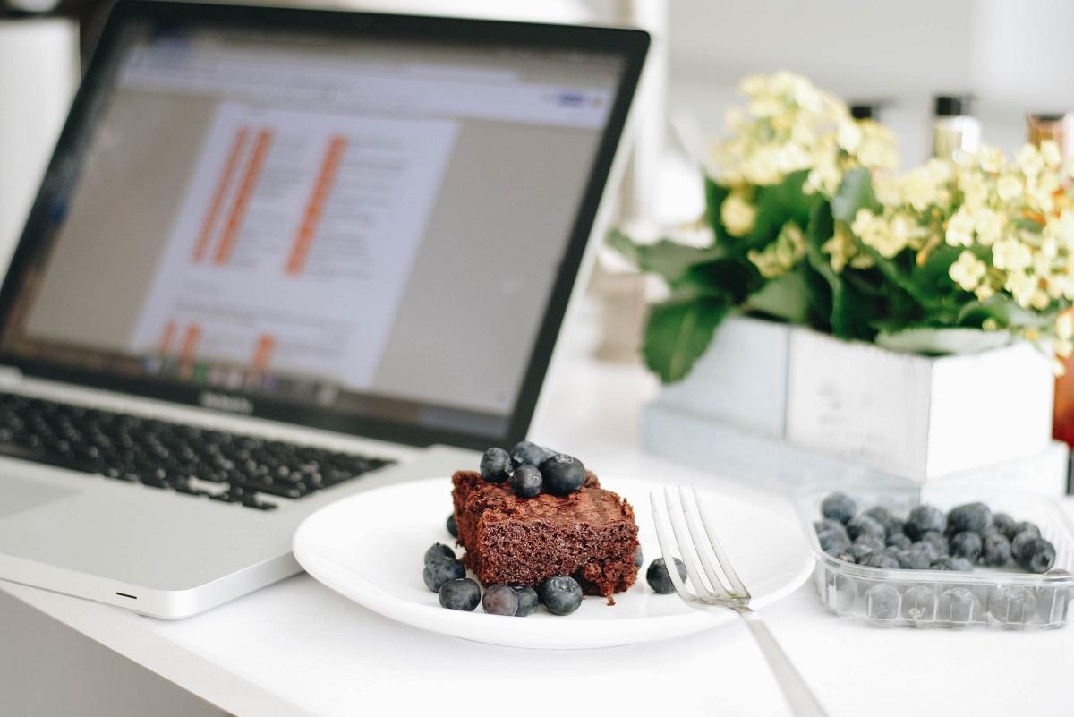 Ordenador, en la oficina, brownie y arándanos, foto de Helena Sollie by Unsplash